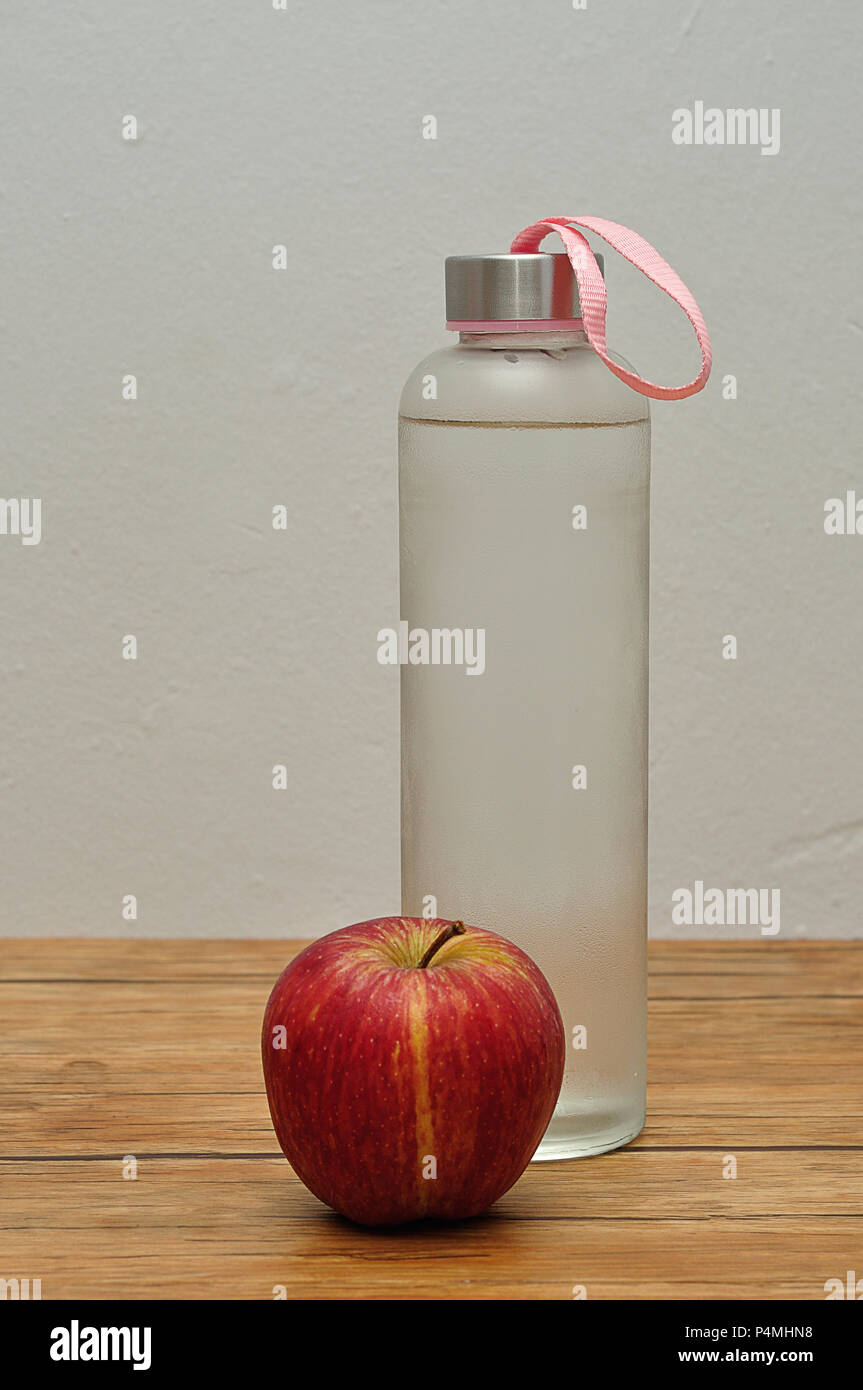 fbd0a8c9c6 A glass bottle filled with ice cold water and an apple Stock Photo ...