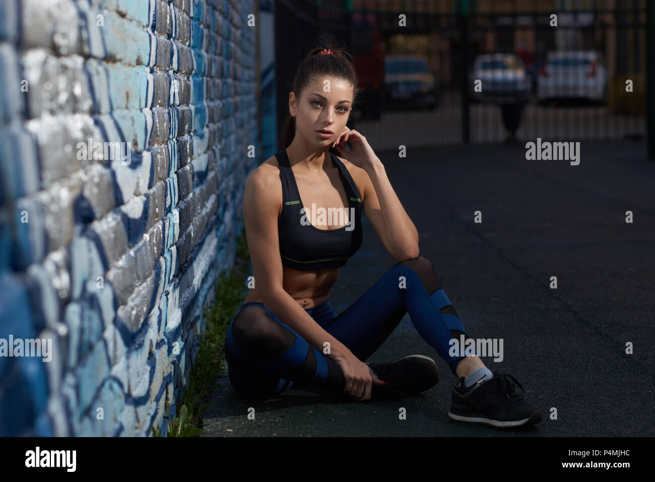 770beaacbd Young beautiful fitness bikini girl in black top and blue leggings sitting  on ground at outdoor workout gym space and looking at you. Sport fitness co