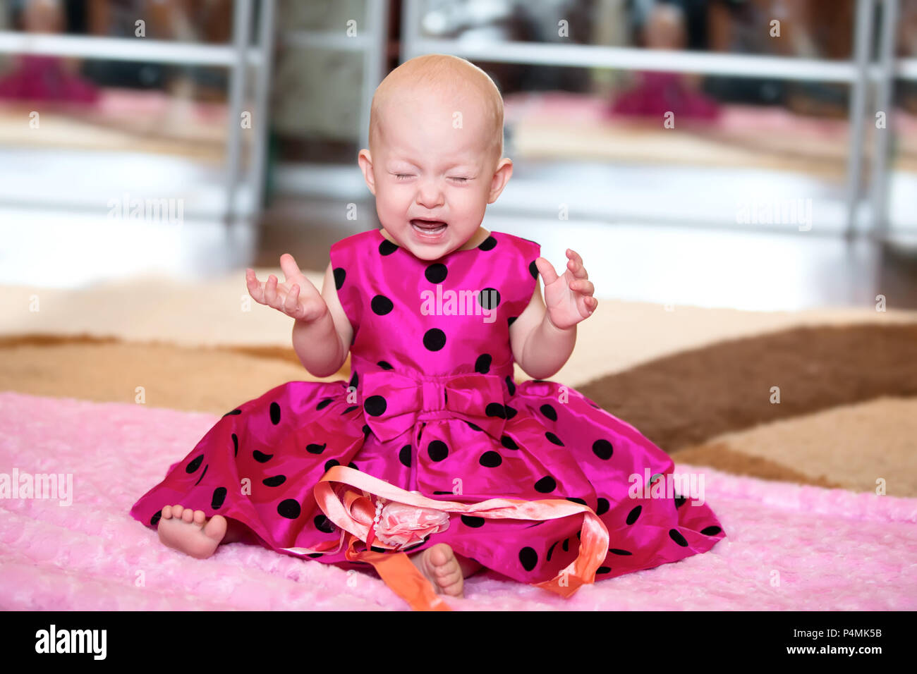 A sobbing little girl in a bright dress. Crying baby - Stock Image
