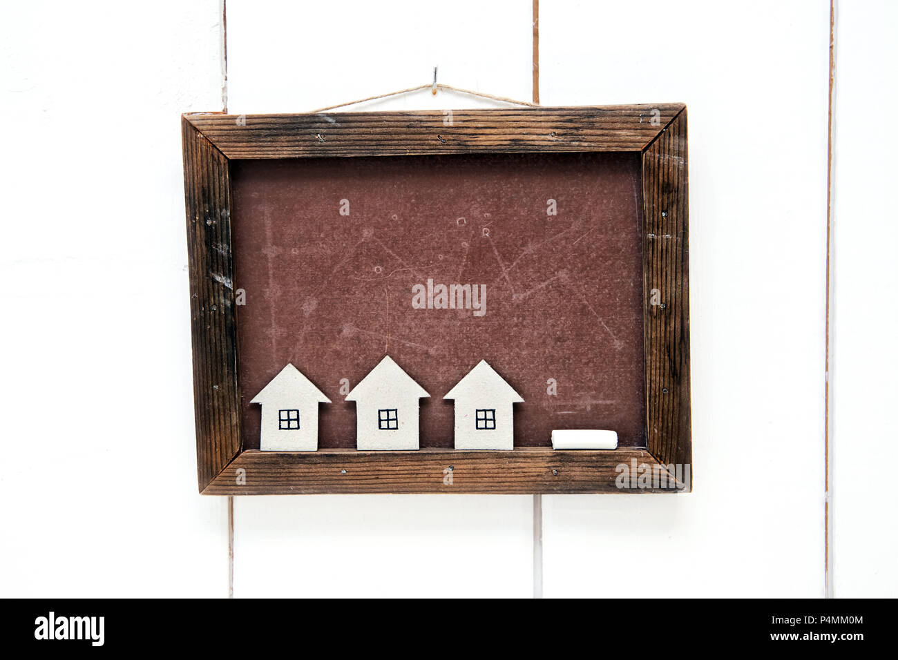 Cardboard houses on a background of a school board. The concept of suburban construction - Stock Image