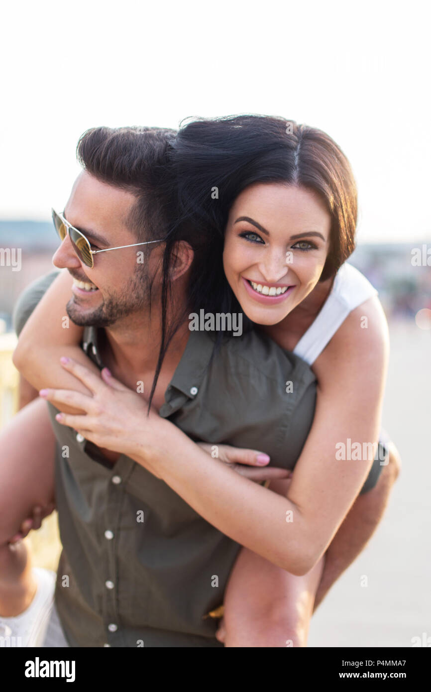 Stylish man carrying girlfriend on back outdoors, couple in fun and happiness - Stock Image