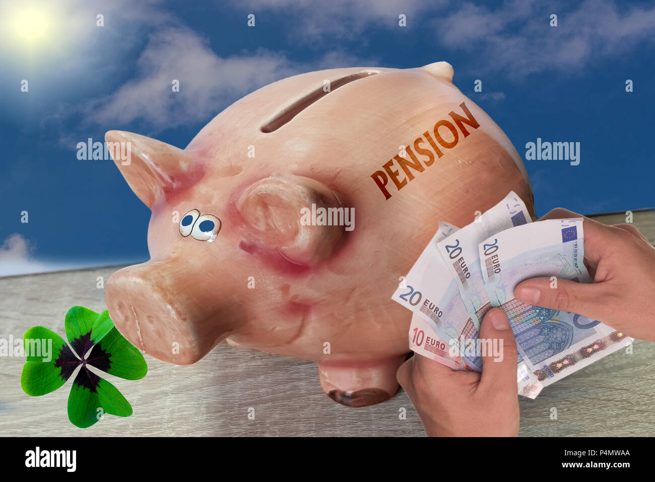 Piggy bank, lucky pig with lettering Pension stands on wooden surface in front of blue sky background. - Stock Image