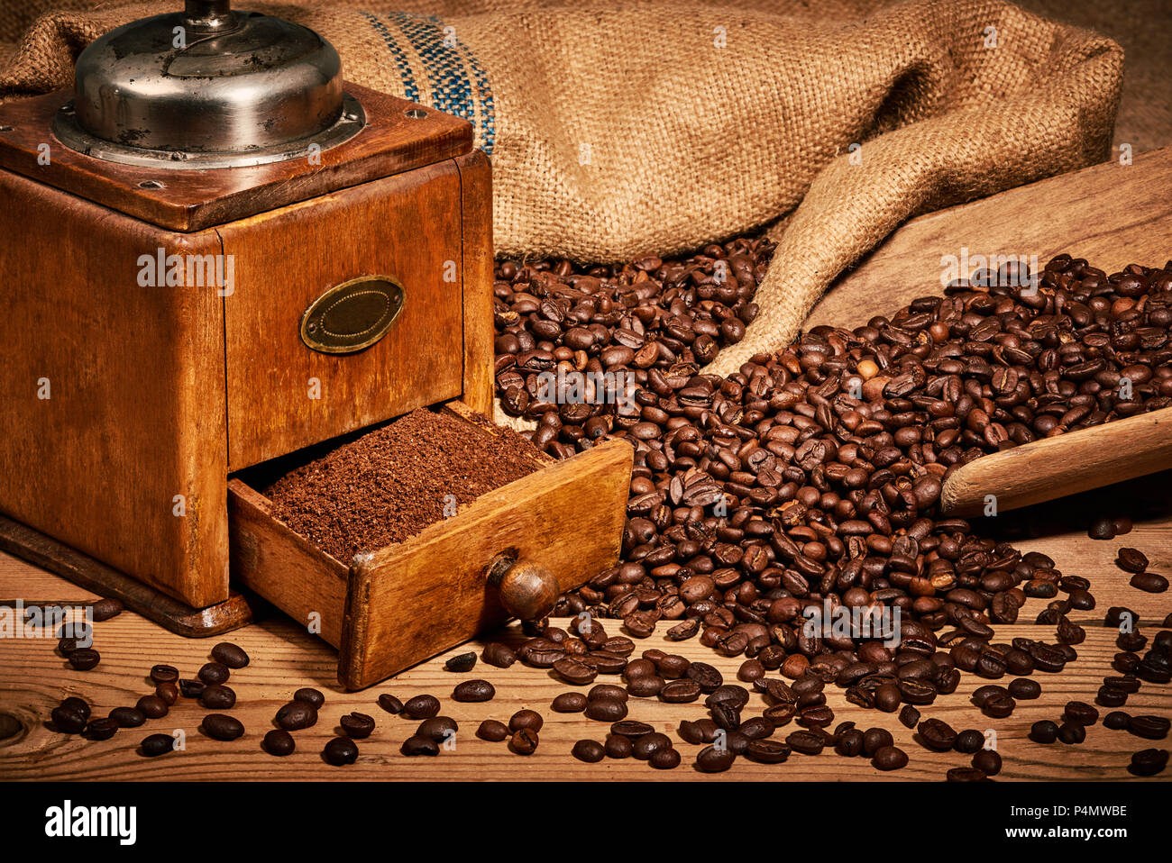 Coffee with old coffee grinder and beans on wooden table - Stock Image