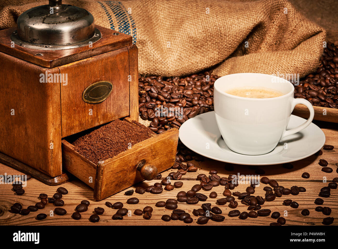 Cup of coffee with old coffee grinder and beans on wooden table - Stock Image