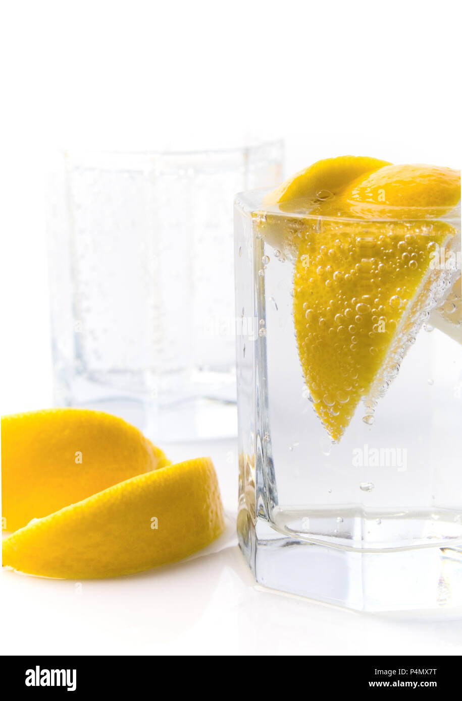 glass with soda water and lemon slices - Stock Image