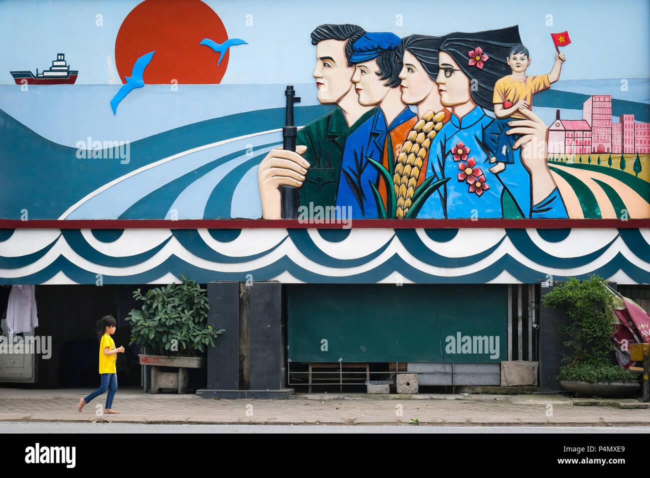 Child under a giant communist propaganda mural in Nam Dinh province, Vietnam - Kind unter einem riesigen kommunistisches Propaganda-Wandgemälde in der Nam Dinh-Provinz, Vietnam - Stock Image