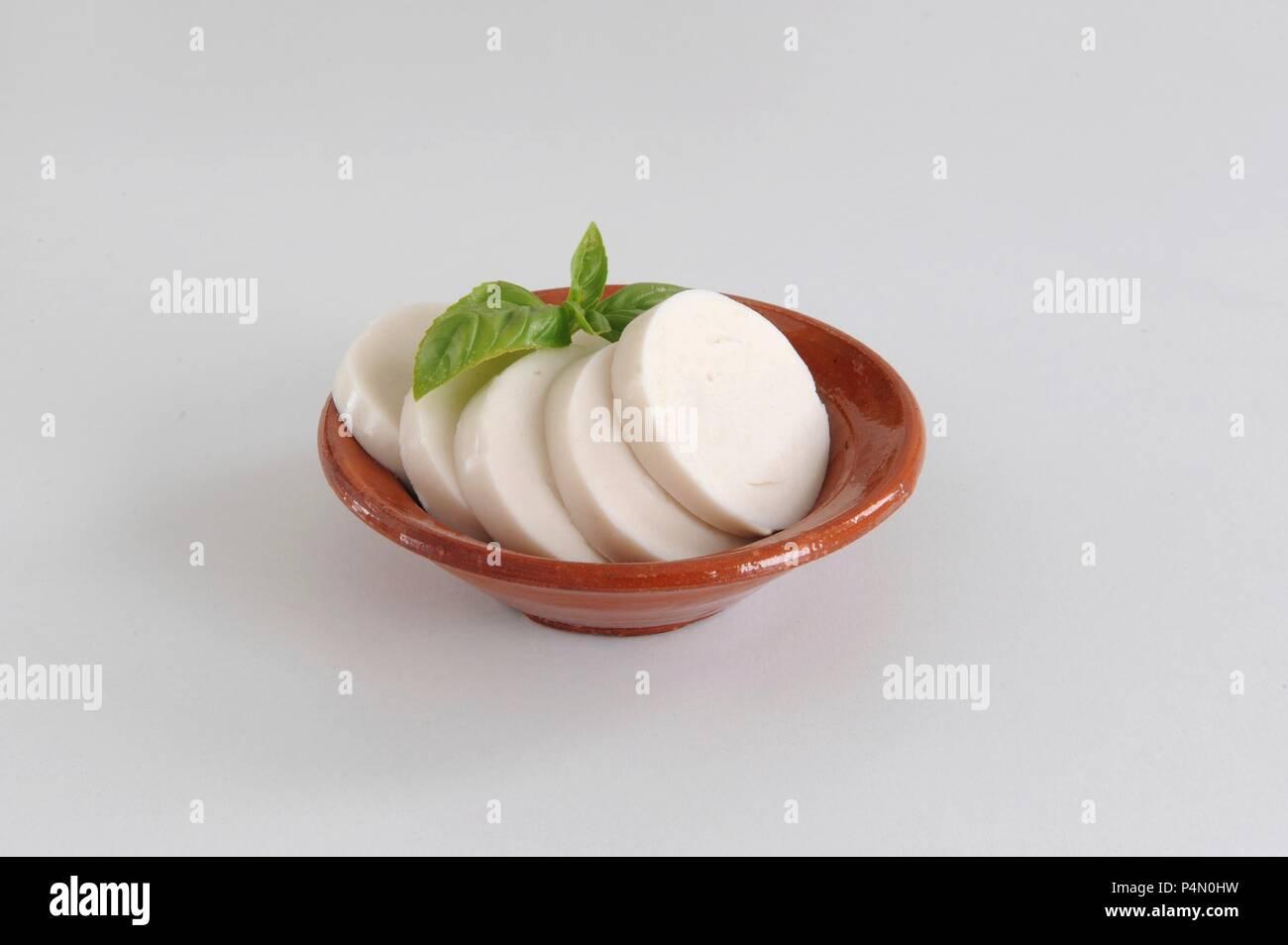 Vegan mozzarella substitute in a terracotta bowl - Stock Image