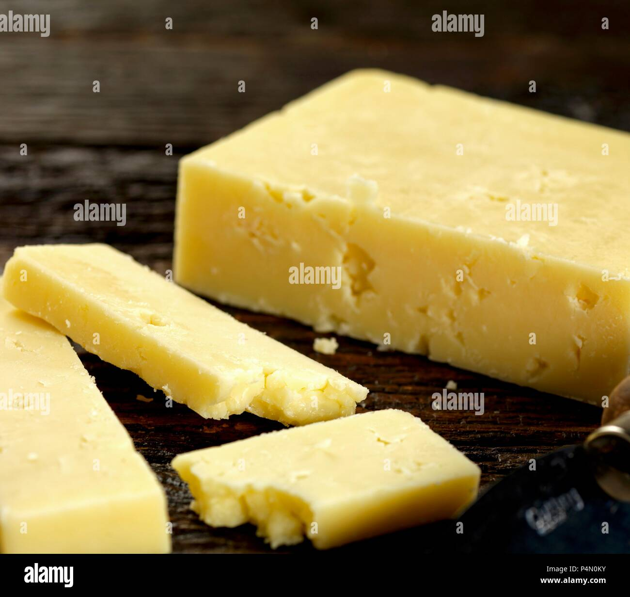 Cheddar cheese on dark wood - Stock Image
