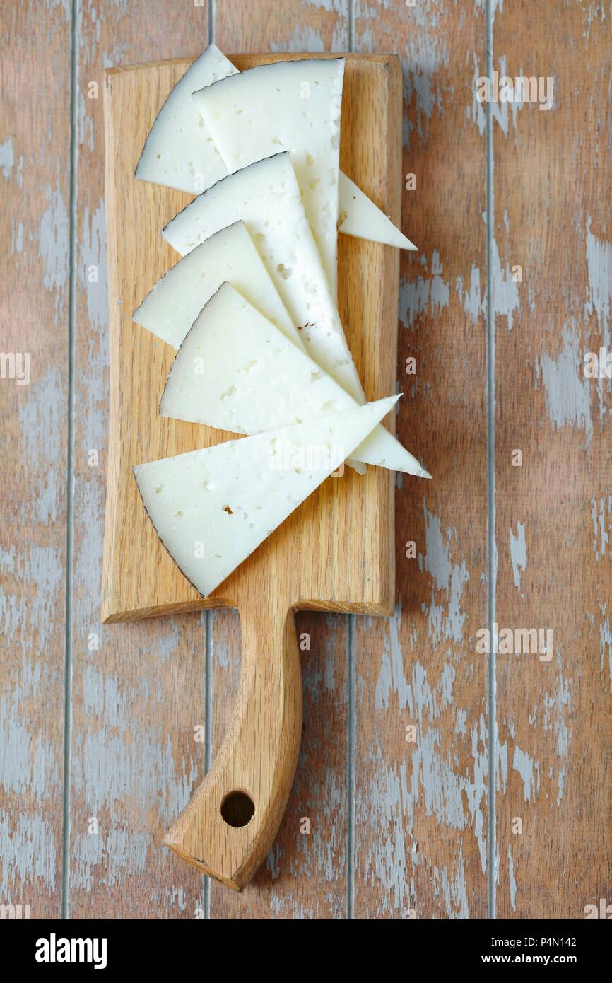 Triangles of Manchego cheese on a chopping board (seen from above) - Stock Image