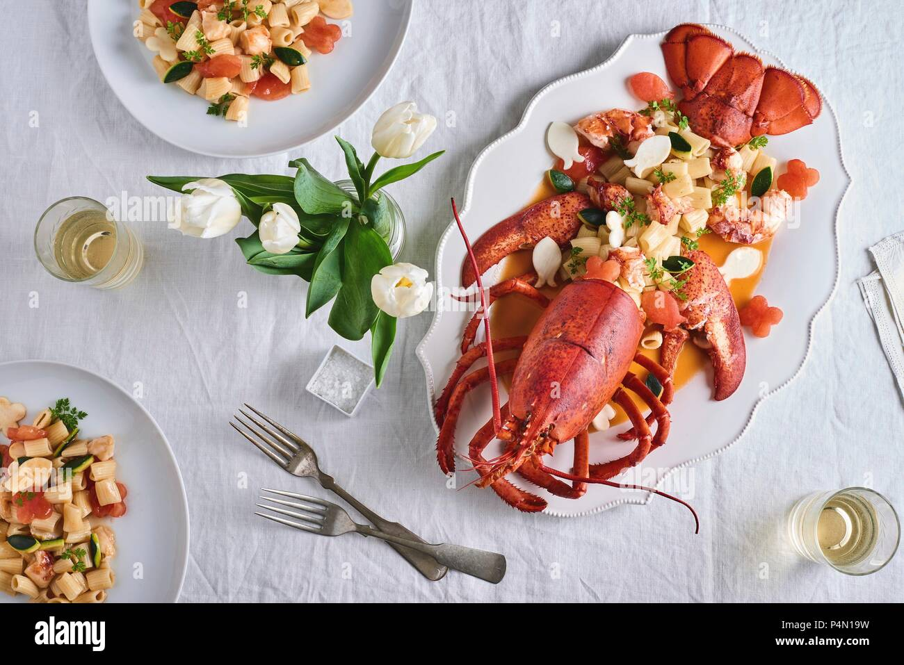 Lobster with rigatoni on a table decorated with a vase of tulips (seen from above) - Stock Image