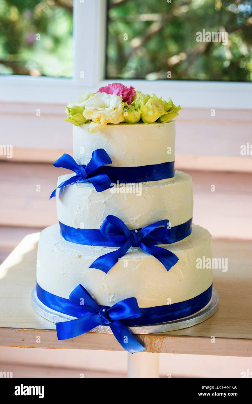 A three-tiered buttercream wedding cake with blue silk ribbons - Stock Image