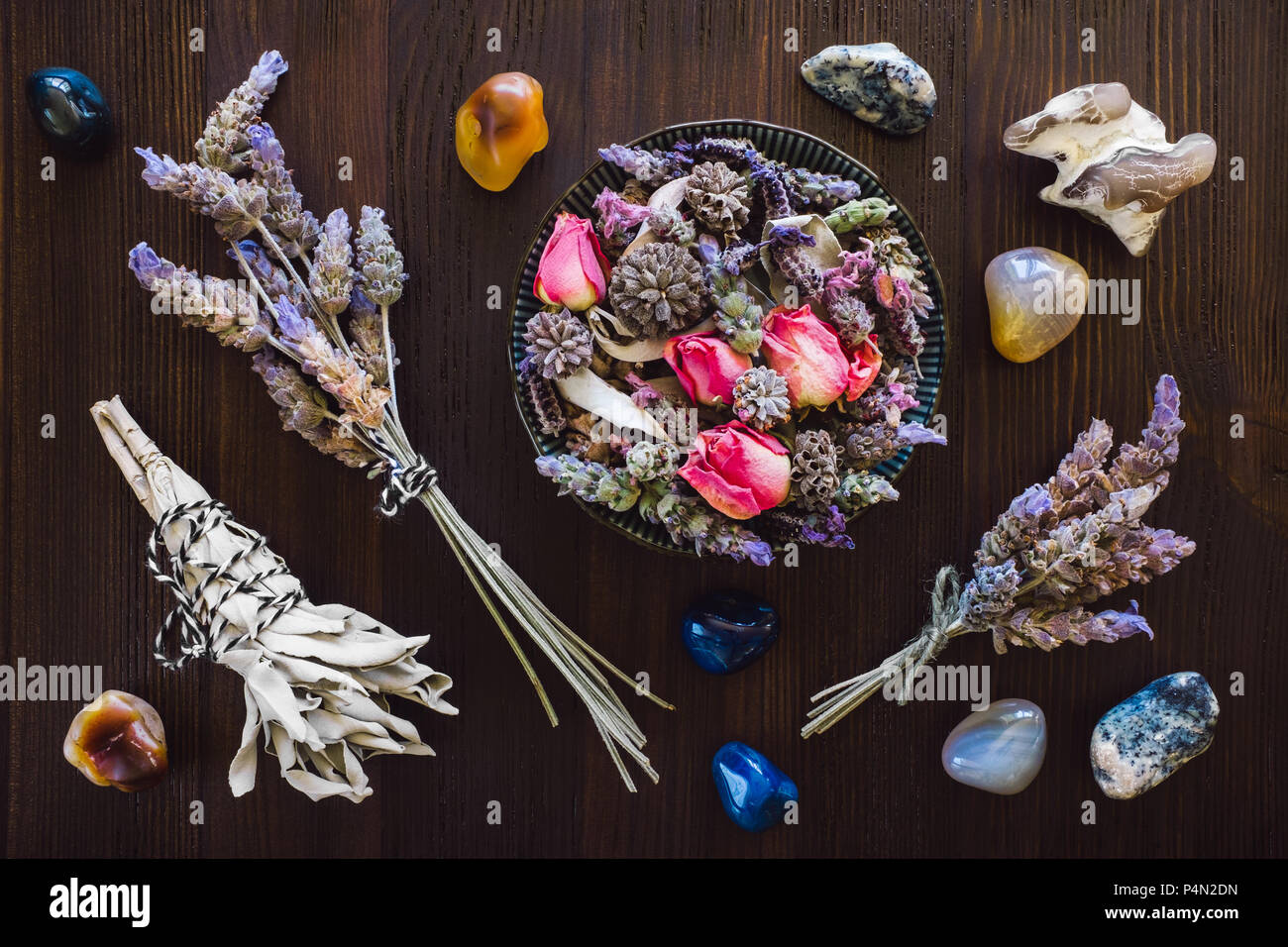 Dried Lavender, Rose and Sage with Agate, Fire Agate, Dendridic Agate and Snakeskin Agate on Dark Wood Table - Stock Image