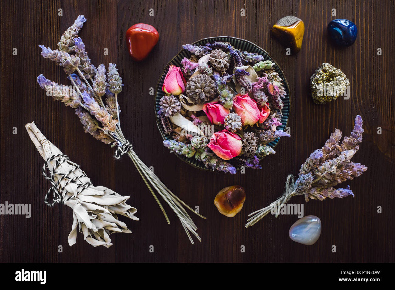 Dried Lavender, Rose and Sage with Red Jasper, Agate, Tiger's Eye and Pyrite on Dark Wood Table Stock Photo