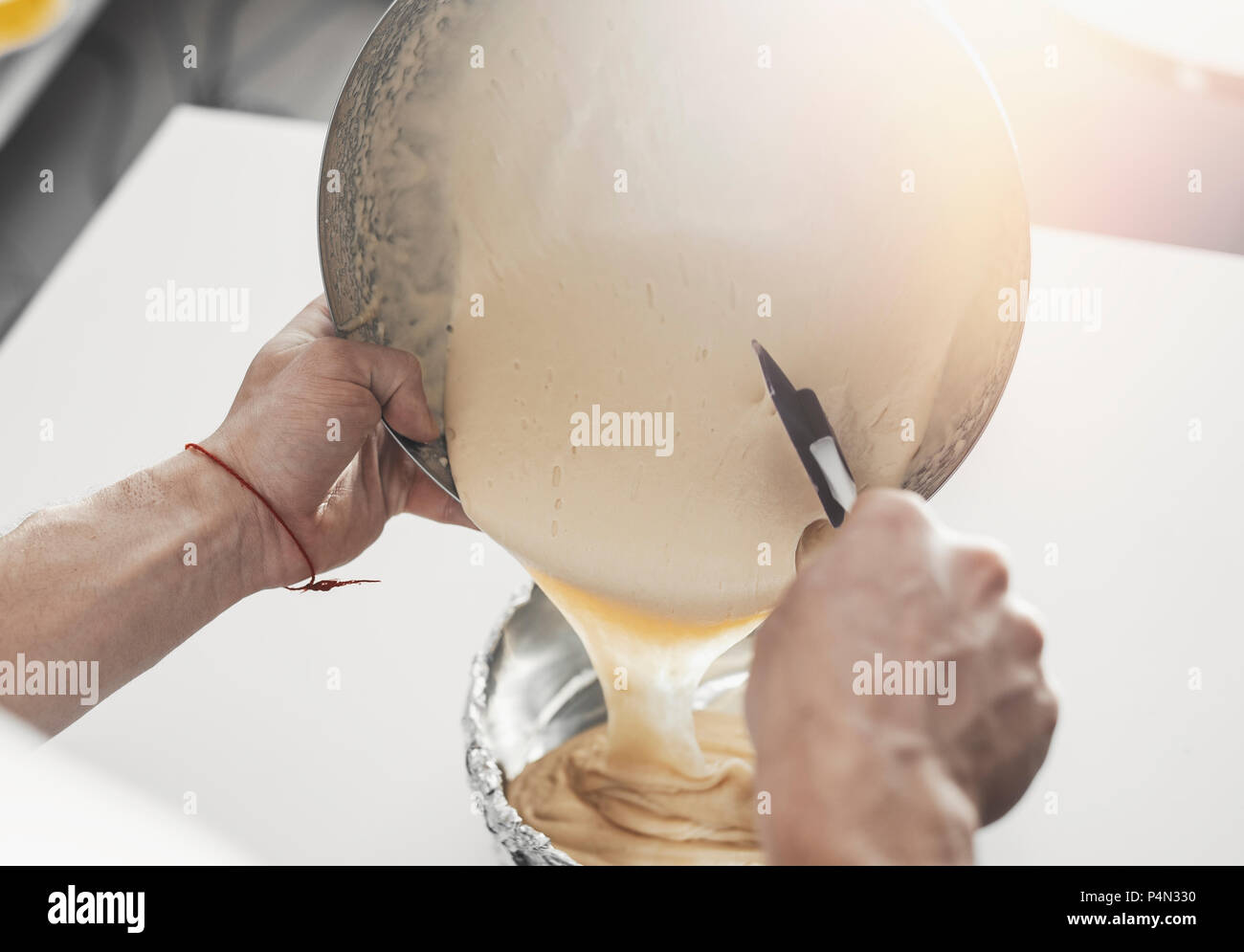 Cook pours dough in big metal plate - Stock Image