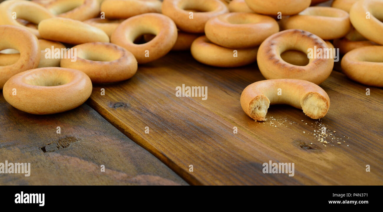 A lot of fresh yellow bagels lie on the surface of the old dark wood. A popular kind of flour products. One of the traditional Russian treats for tea  Stock Photo