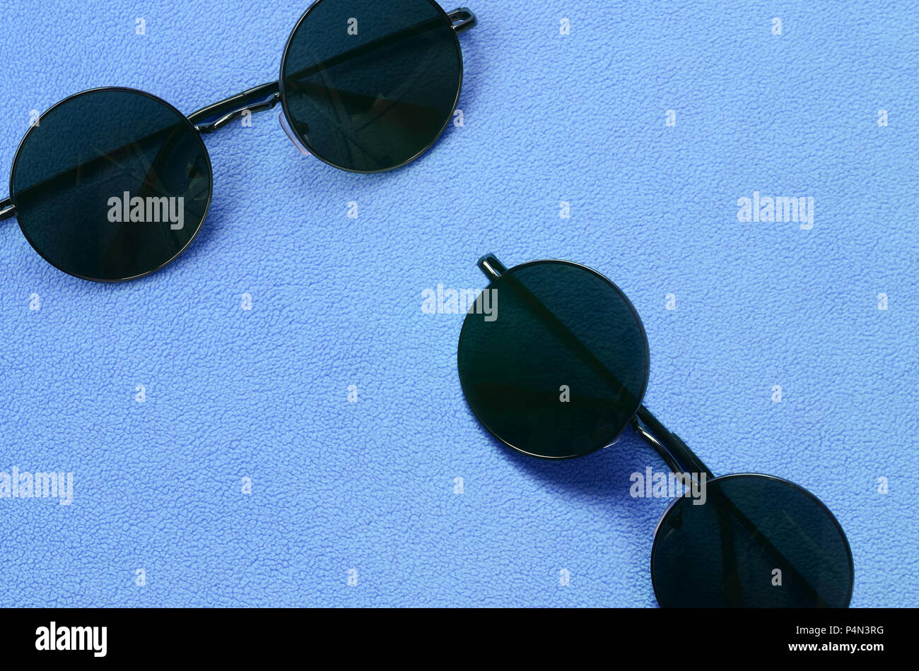 4d88b5c93647 Two stylish black sunglasses with round glasses lies on a blanket made of  soft and fluffy light blue fleece fabric. Fashionable background picture in