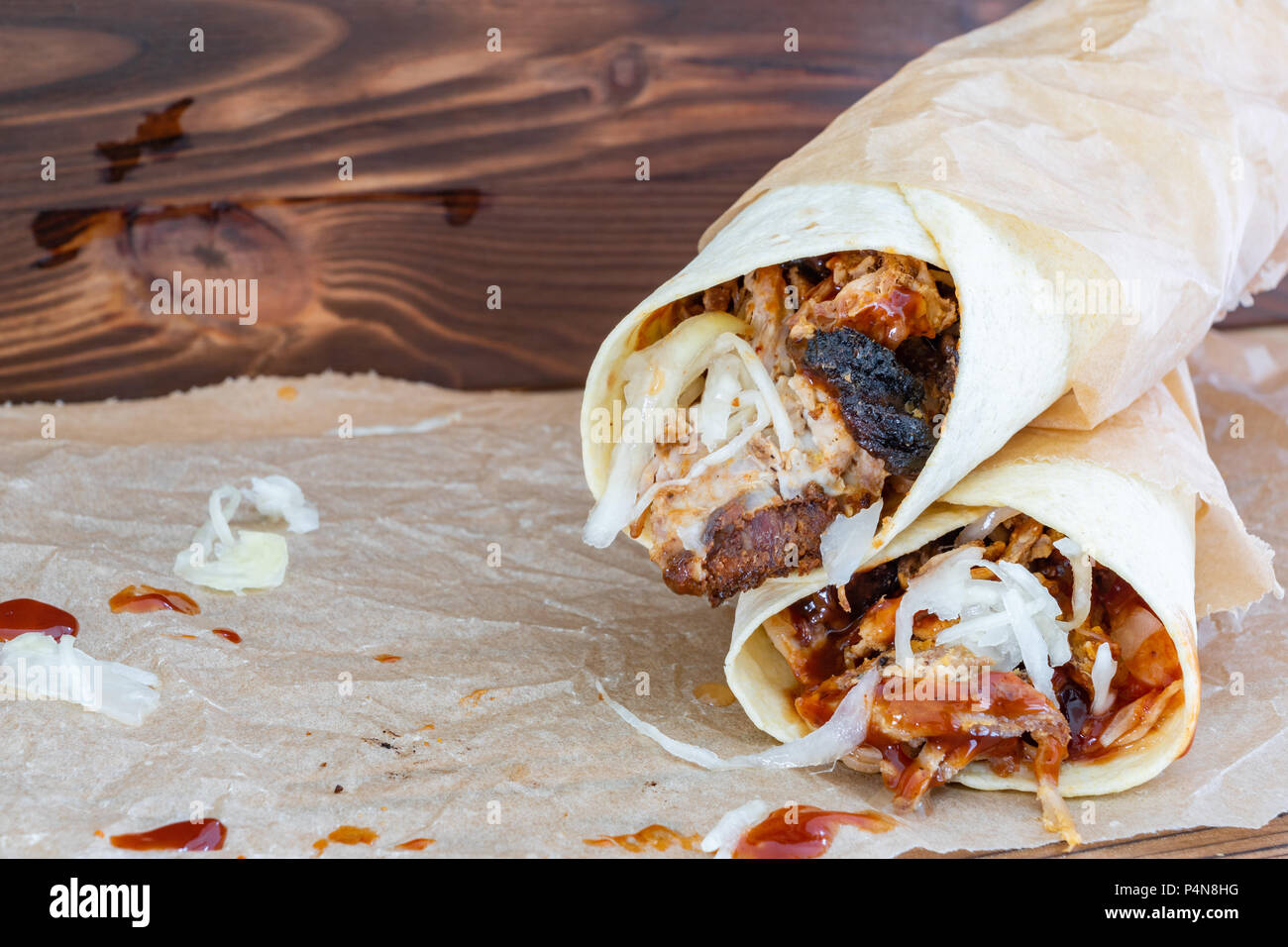 Pulled Pork Wraps with hot BBQ sauce on a wooden tabel - Stock Image