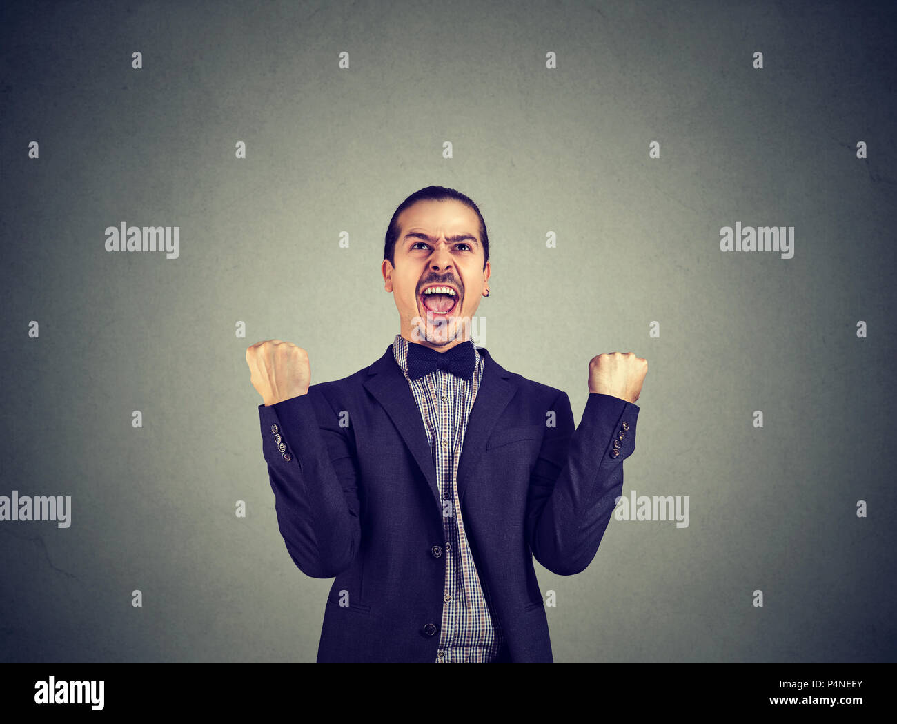 Excited formal man in suit holding fists up and celebrating success and new achievement shouting on gray background - Stock Image