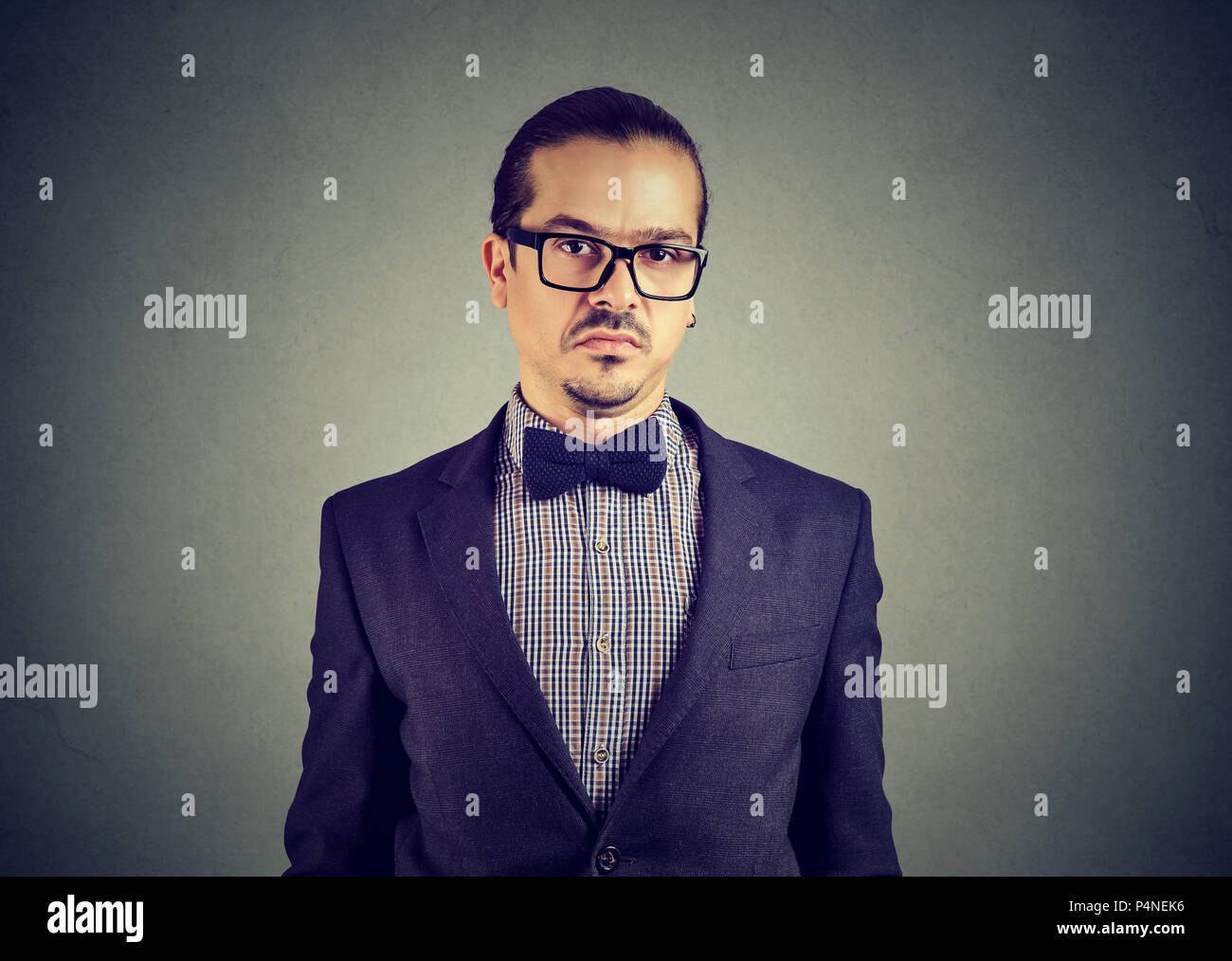 Young elegant man in glasses looking skeptically at camera full of doubts on gray background - Stock Image