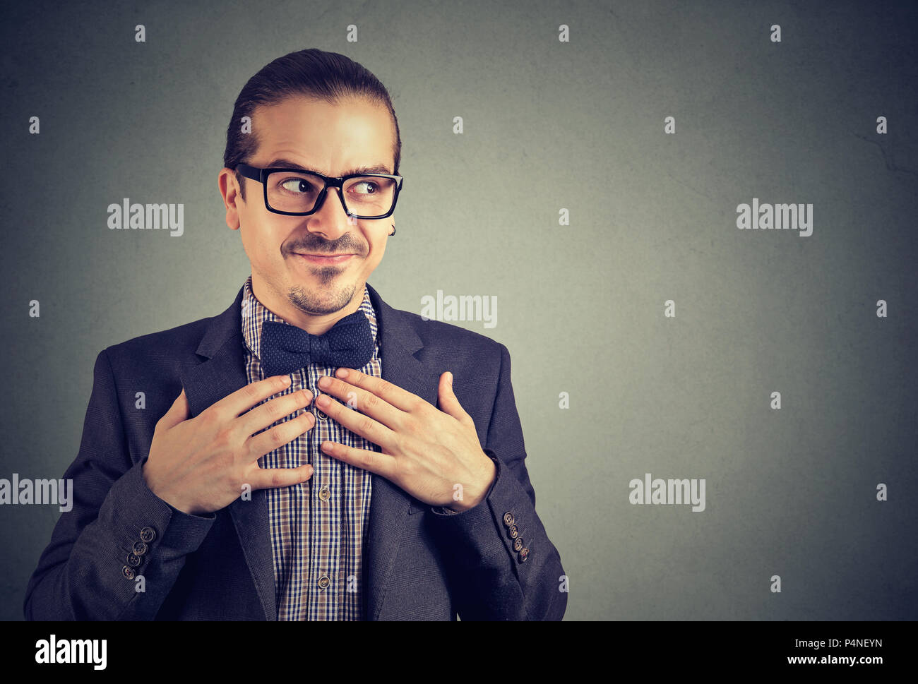 Young crazy man in glasses and suit looking nerdy away holding hands on chest in shyness on gray background - Stock Image