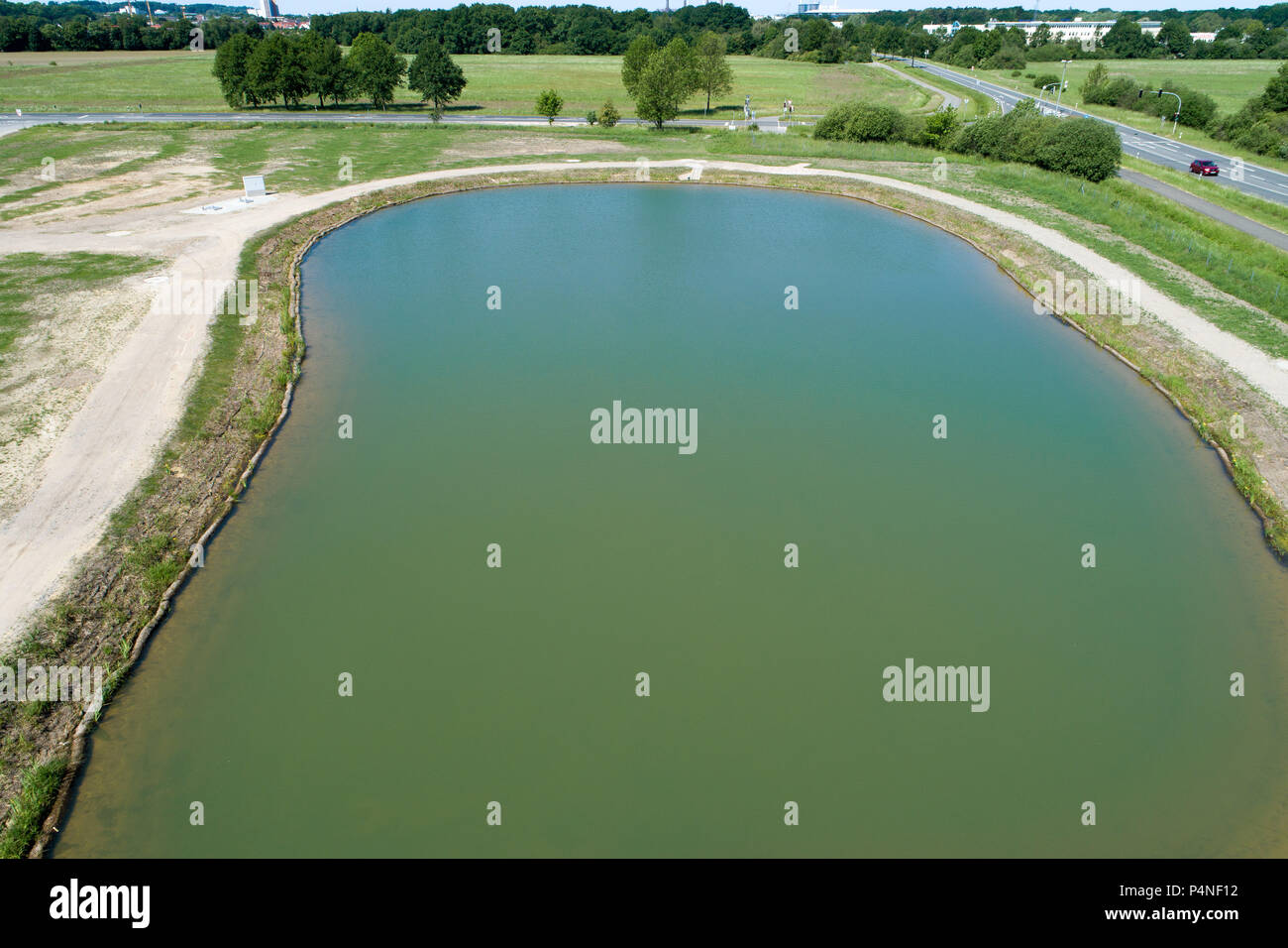 Rainwater retention basin with turquoise coloured water, taken diagonally from the air with a drone, Germany - Stock Image