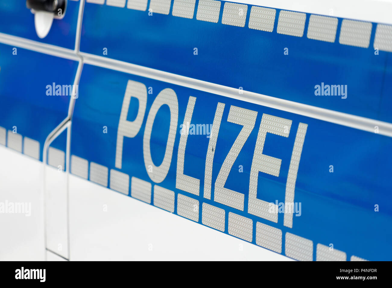 Inscription 'Police' in white luminous colour on a blue background on the side of a police car, Germany - Stock Image