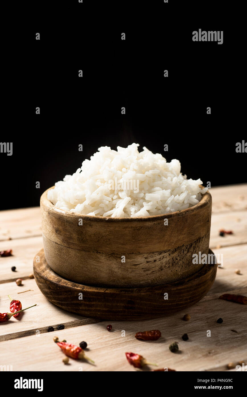 closeup of a boxwood bowl with some cooked long grain rice, on a rustic wooden table, against a black background, with some blank space on top - Stock Image