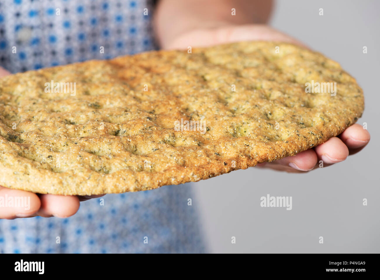 closeup of a caucasian man with a kale flatbread in his hands - Stock Image