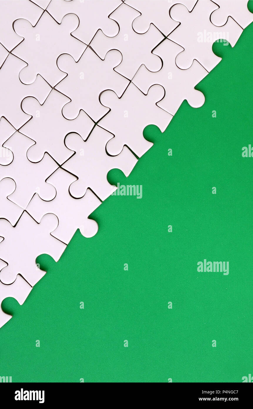 Fragment of a folded white jigsaw puzzle on the background of a green plastic surface. Texture photo with copy space for text - Stock Image