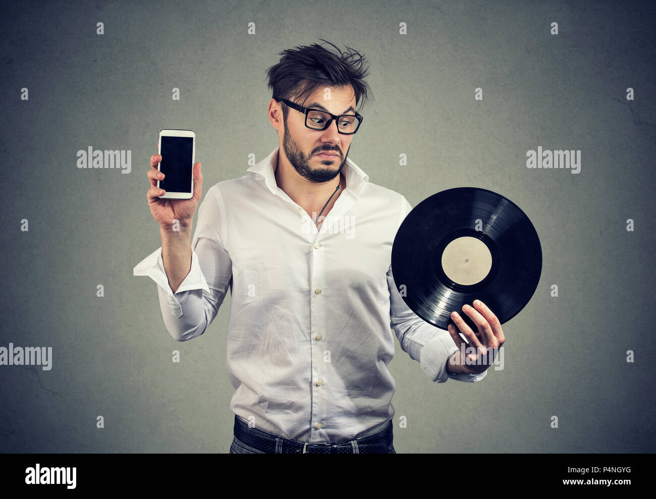 Young bearded man in glasses looking puzzled while choosing between vinyl disk and smartphone - Stock Image