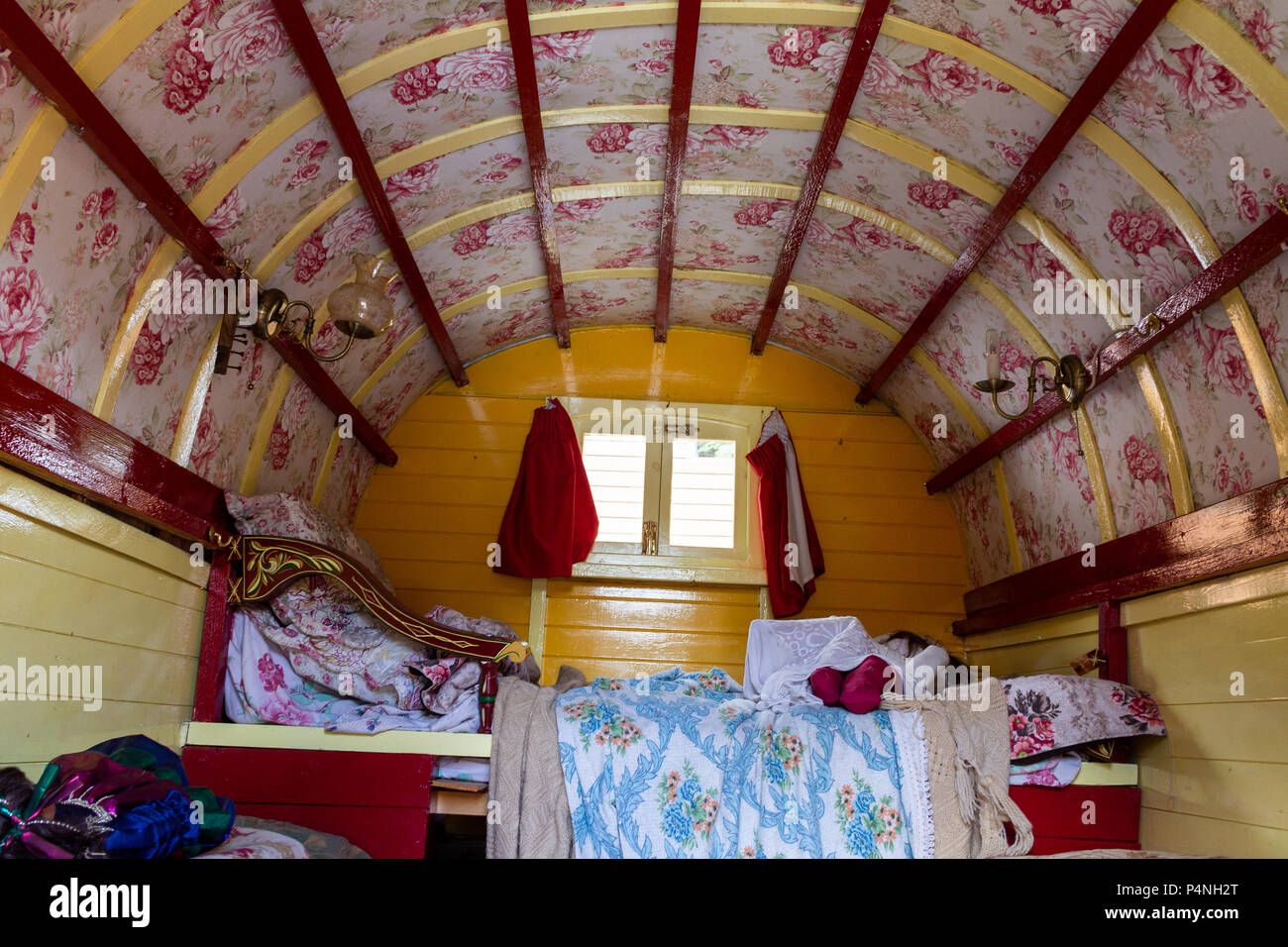 Inside a gypsy caravan showing the floral paintwork and colourful decoration. - Stock Image