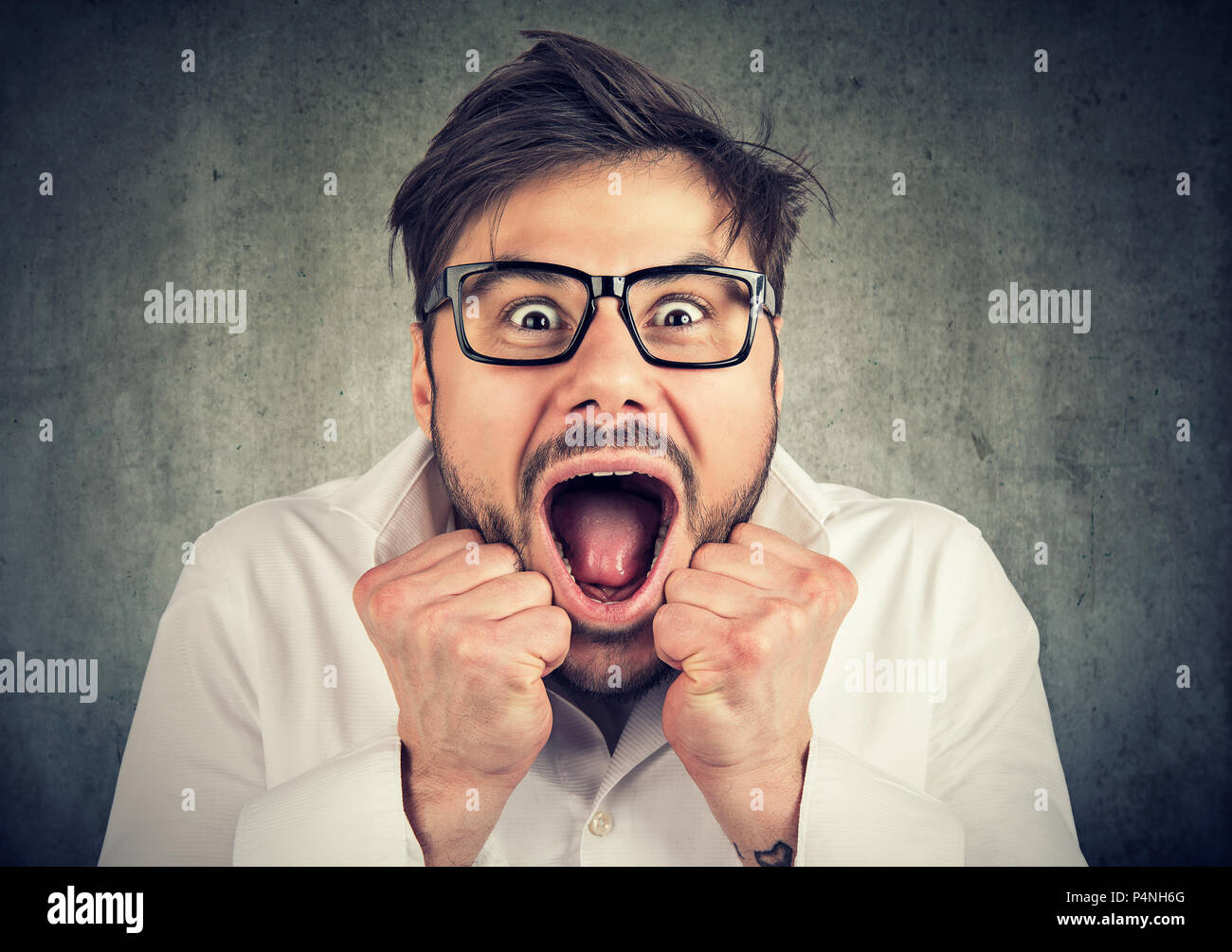 Close-up of young man in glasses with mouth opened thrilled to scream with surprise and looking at camera on gray background - Stock Image