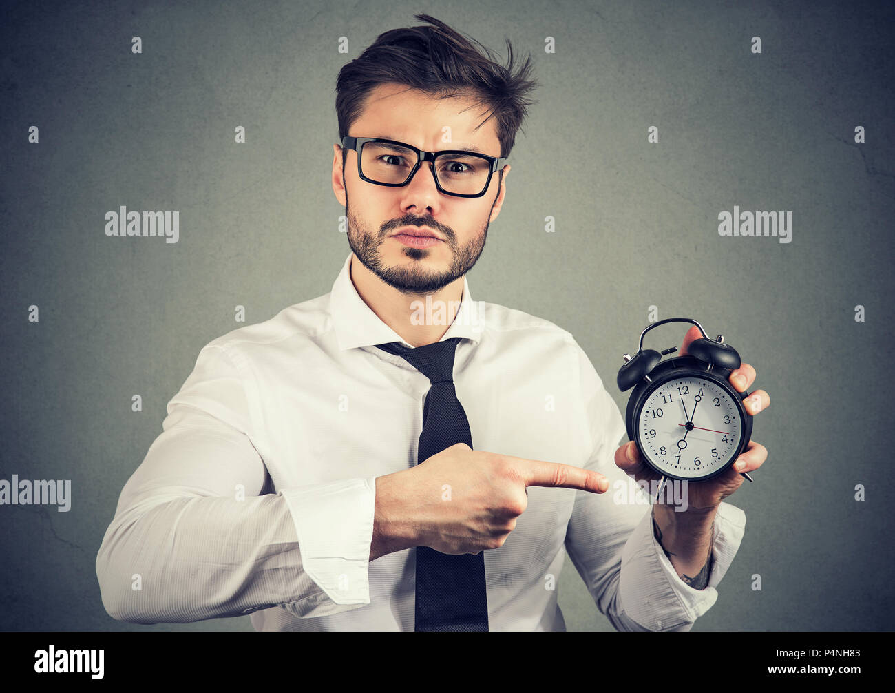 Adult formal man in glasses looking seriously at camera and pointing at clock showing time on gray background - Stock Image