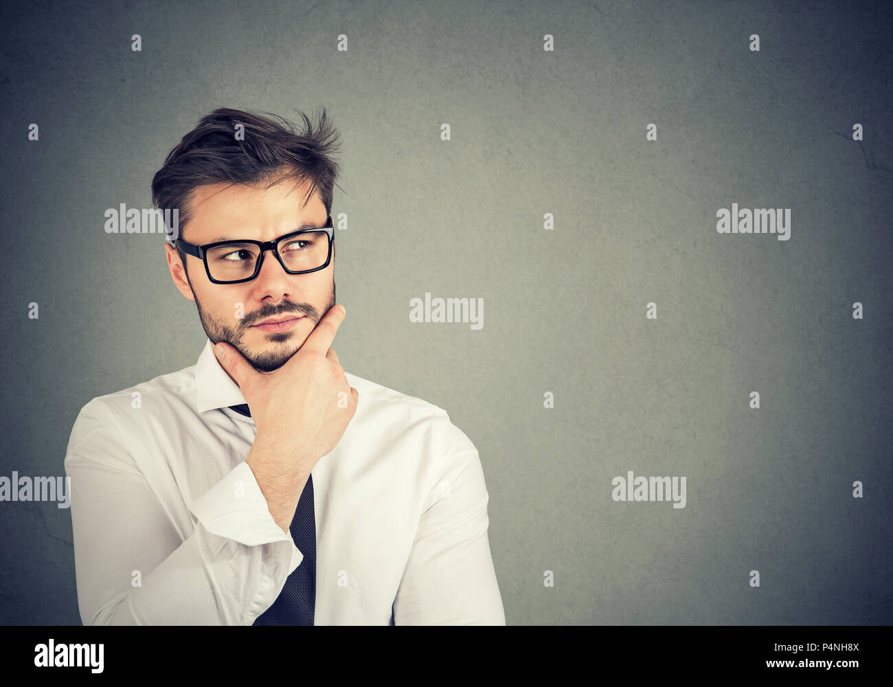 Young bearded man in contemplation looking up and planning new business strategy and creating idea on gray background - Stock Image