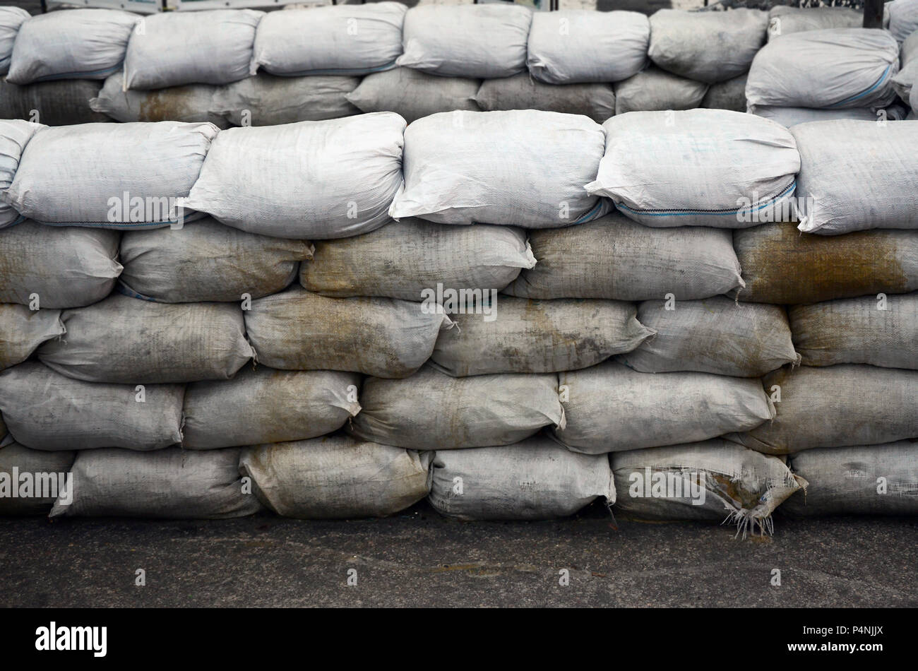 Background of many dirty sand bags for flood defense. Protective sandbag barricade for military use. Handsome tactical bunker . Stock Photo