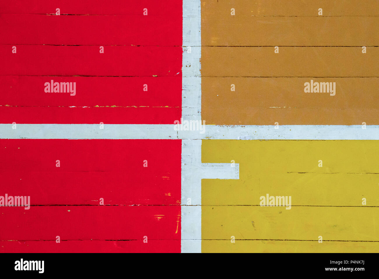 Worn out wooden floor of sports hall with colorful marking lines - Stock Image