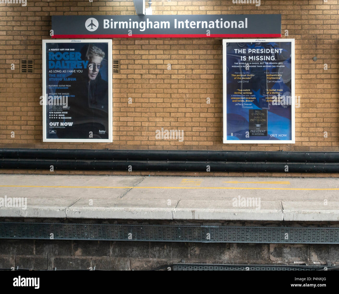 Platform at Birmingham International Airport station, with posters for Roger Daltrey's As Long as I Have You album and The President is Missing. - Stock Image