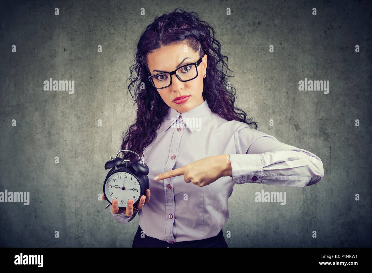 Business woman in glasses looking seriously at camera and pointing at alarm clock showing time on gray background - Stock Image
