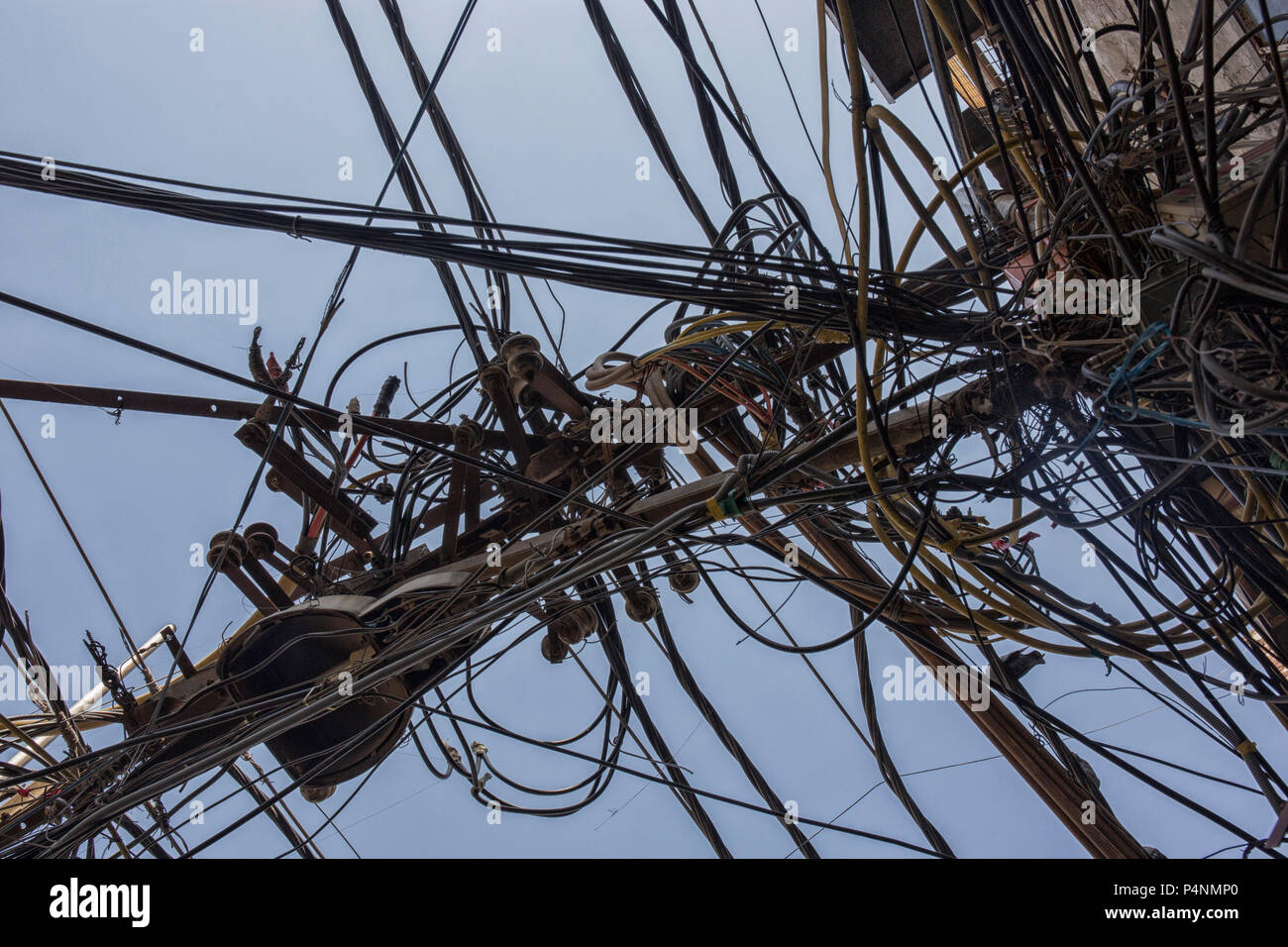 Wires attached to the electric pole, the chaos of cables and wires on an electric pole in New dehli, India, concept of electricity - Stock Image