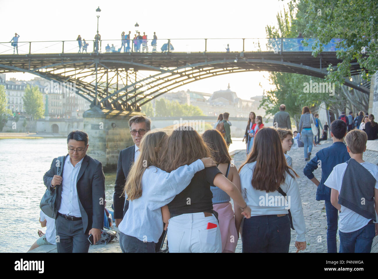 Paris, France, Young generation taking for a walk with a background of a bridge, Pont des Arts (Bridge of the Arts) - Stock Image