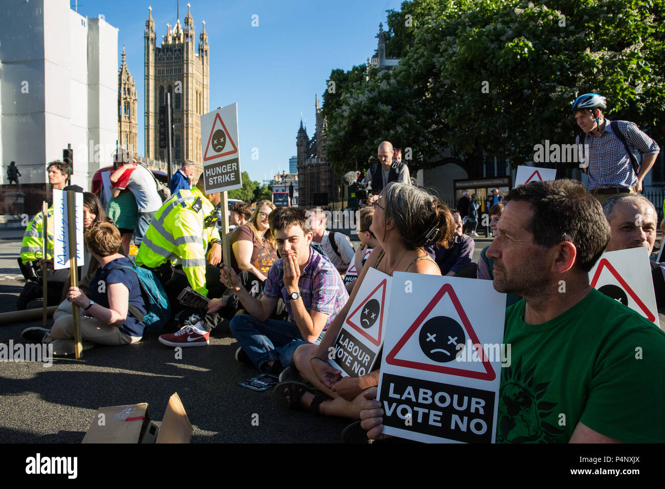 London, UK. 22nd June, 2018. Campaigners from Vote No Heathrow, some of whom have been on hunger strike for 14 days, block the road in Parliament Square to protest against the Government's plans to allow, and the lack of Labour opposition to, a third runway at Heathrow airport. A vote on the issue is to be held in the House of Commons on Monday and the campaigners have in particular been calling on the Labour Party to whip its MPs to oppose Heathrow expansion. Stock Photo