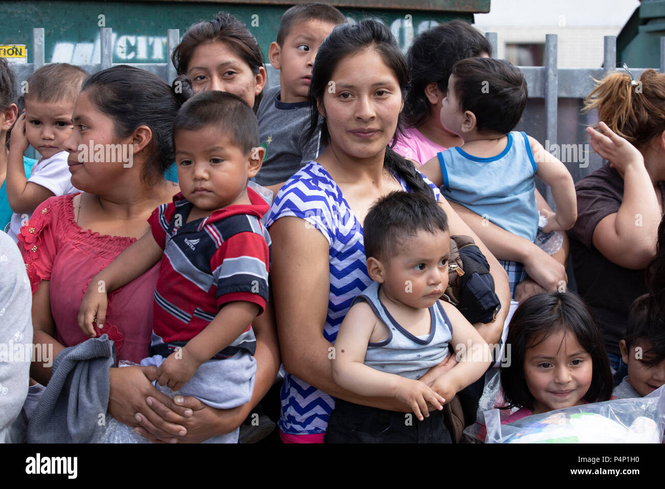 Immigrant mothers, wearing electronic monitoring devices, and their young children captured coming across the United States-Mexico border in Texas are released at a bus station in McAllen. The families will travel to stay with family members in the U.S. while awaiting deportation or asylum hearings. - Stock Image