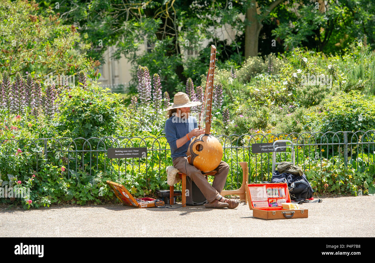 Brighton UK 23rd June 2018 - A musician busks in Pavilion Gardens Brighton on a beautiful sunny day with temperatures set to soar throughout Britain over the next few days Credit: Simon Dack/Alamy Live News - Stock Image