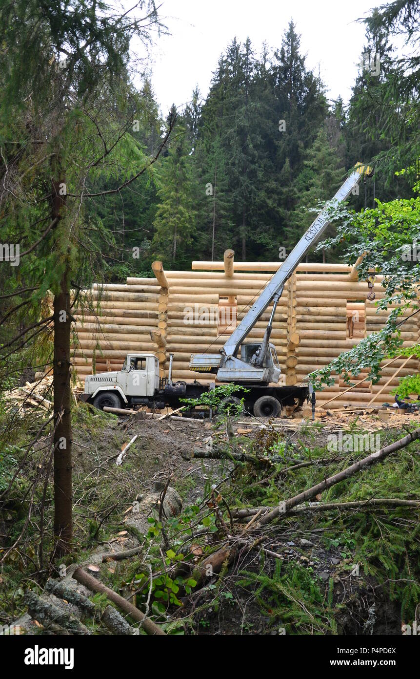The process of building a wooden house from wooden beams of cylindrical shape. Crane in working condition. - Stock Image
