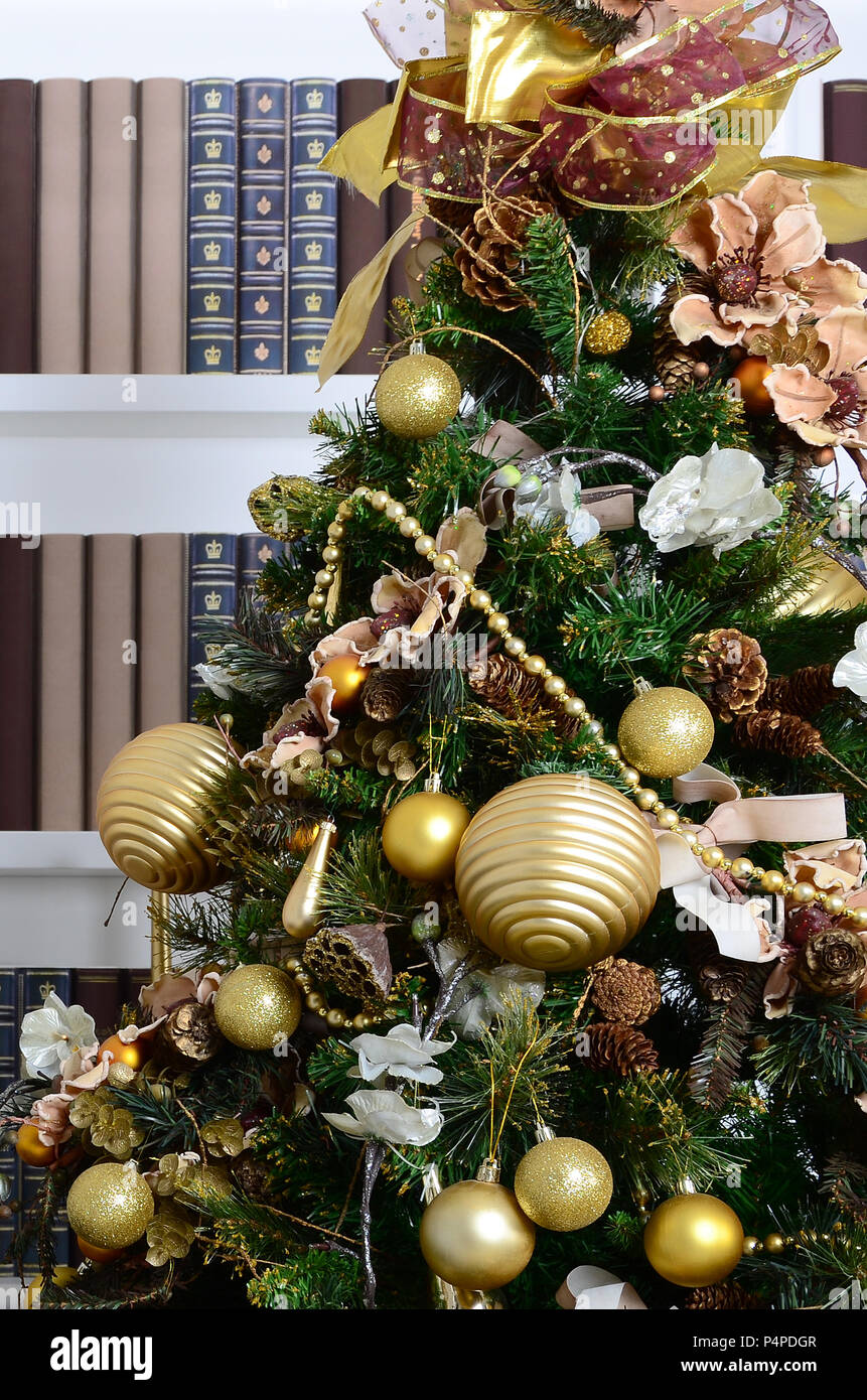 A Beautiful Decorated Christmas Tree On The Background Of Bookshelf With Many Books Different Colors Image Library
