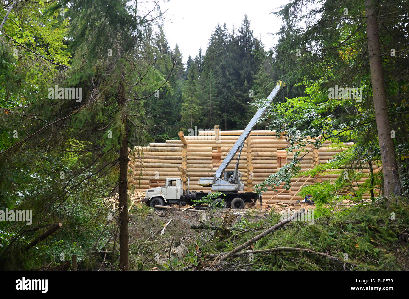 The process of building a wooden house from wooden beams of cylindrical shape. Crane in working condition - Stock Image