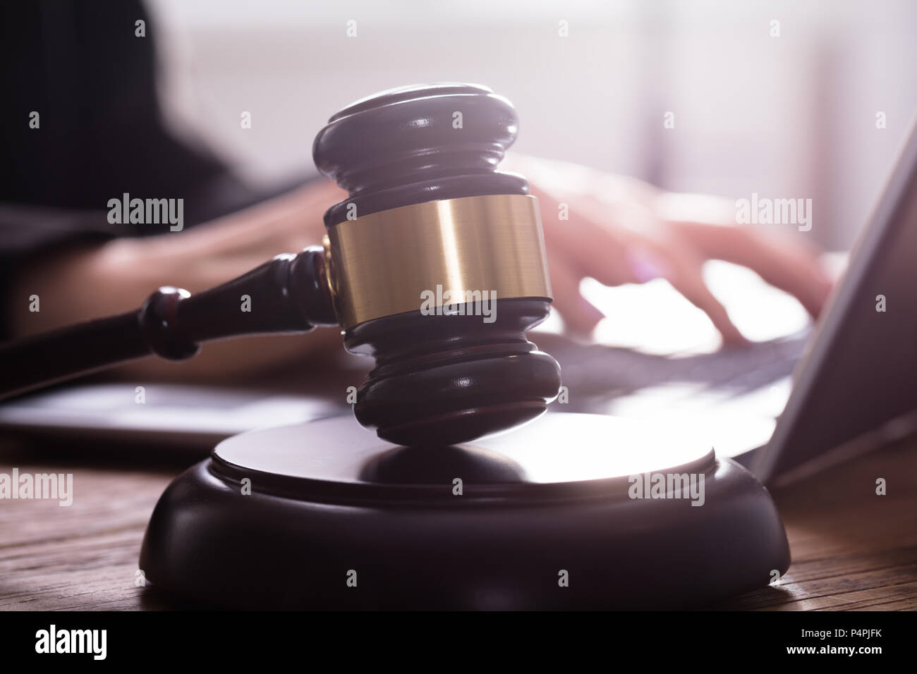 Close-up Of A Gavel On Sounding Block In Front Of Judge Using Laptop - Stock Image