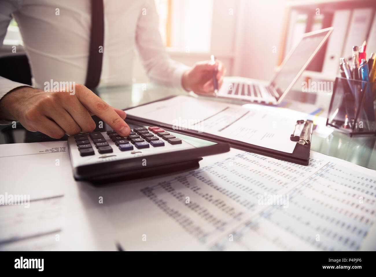 Close-up Of A Businessman Checking Invoice Over Desk - Stock Image