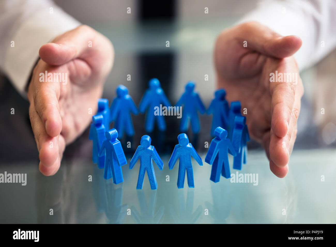 Close-up Of A Businessperson's Hand Protecting Blue Human Figures Forming Circle Stock Photo