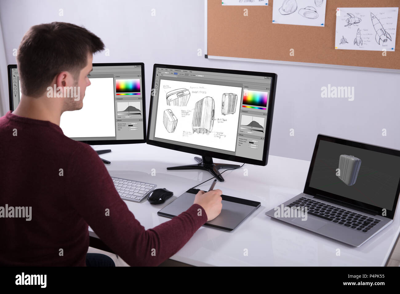 Side View Of Designer Drawing Suitcase On Computer Using Graphic Tablet In Office - Stock Image